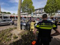 Automobilist rijdt plantsoen in bij winkelcentrum