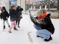 Kinderen spelen met juf in de sneeuw school Keerkring Dordrecht