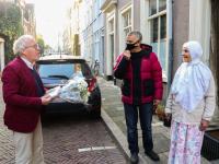 Frits Baarda reikt boek uit aan oudste bewoonter Hoge Nieuwstraat Dordrecht